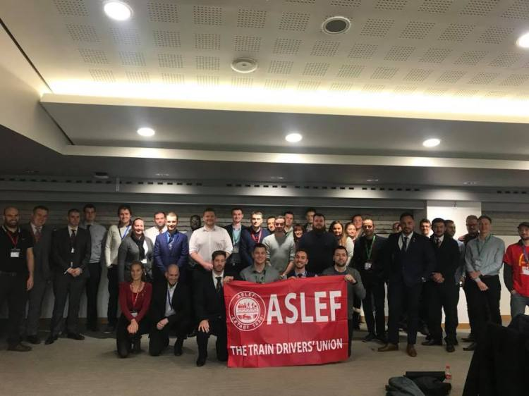 A group of about 30 people standing together in a hotel conference room. A smaller group at the front are kneeling down and holding a red ASLEF flag.
