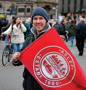Craig Cameron is wearing a hoody, coat and warm hat. He is in a crowded street and holding a red ASLEF flag.