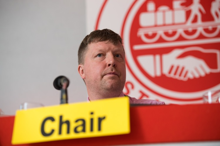 Darran Brown sits at a red desk in front of an ASLEF logo. A yellow card in front of his microphone says Chair.