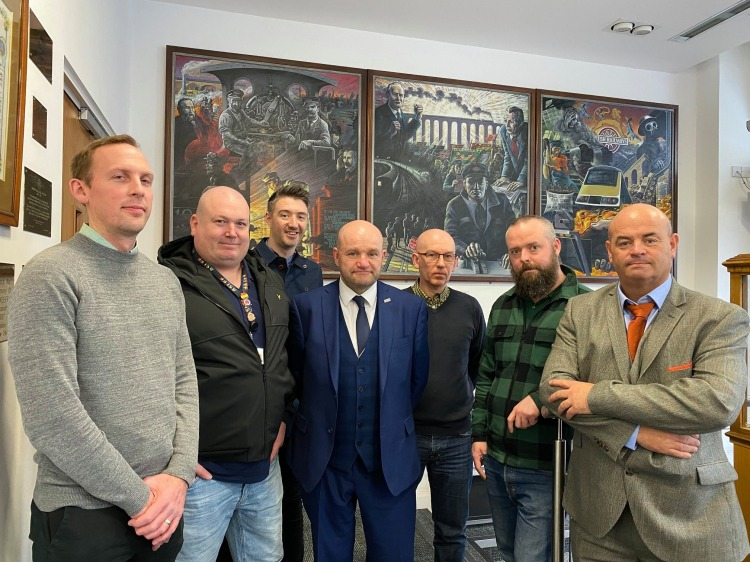 A group of seven people stand together in the foyer of ASLEF Head Office. Behind them are three large paintings of railway history.