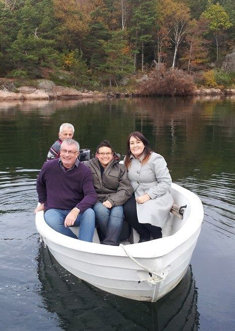 Four people sit in a white boat on a lake
