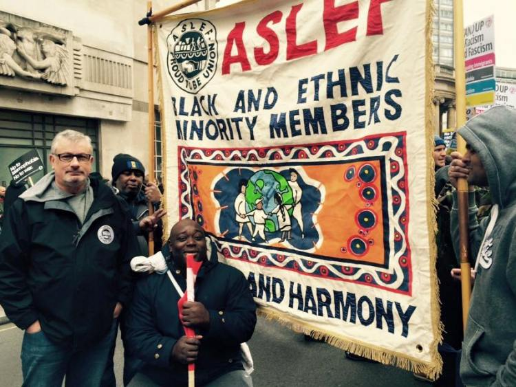ASLEF's Black and Ethnic Minority Members banner is in the centre of the photograph, being held by two people. Two other ASLEF members are standing in front of the banner.