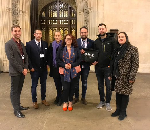 A group of young ASLEF members stand with Danielle Rowley in Westminster Hall in Parliament, in front of an ornate door.