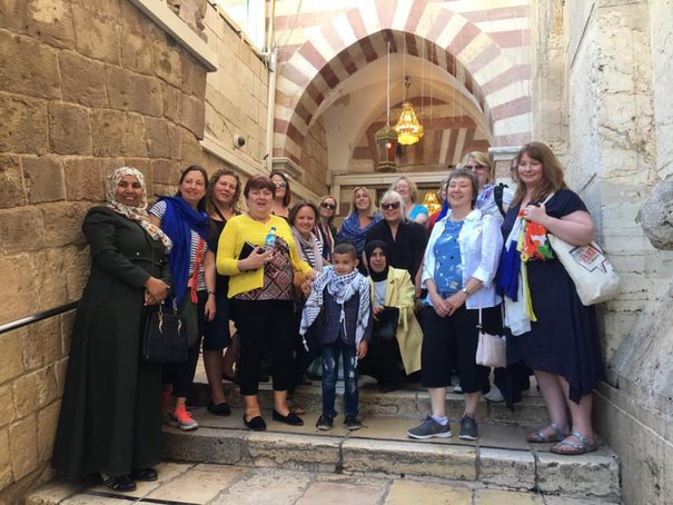 A group of smiling British and Palestinian women and children stand, grouped together, in front of a large stone archway.