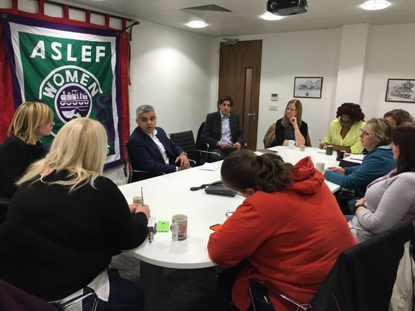 Members of ASLEF's women's representative committee sit around a large table with Sadiq Khan. The ASLEF women banner is leaning on the wall behind them.