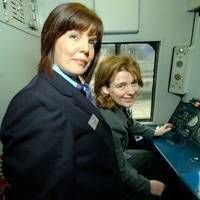 Ruth Kelly sits in front of the controls of a train cab. Pauline Cawood is standing on the left of the photo in her uniform.