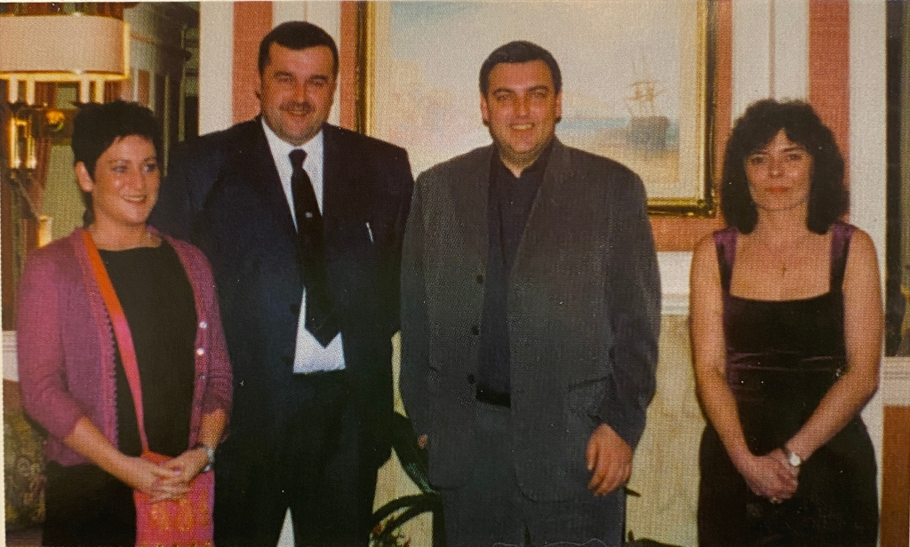 Two women and two men in smart clothing stand in a row smiling at the camera