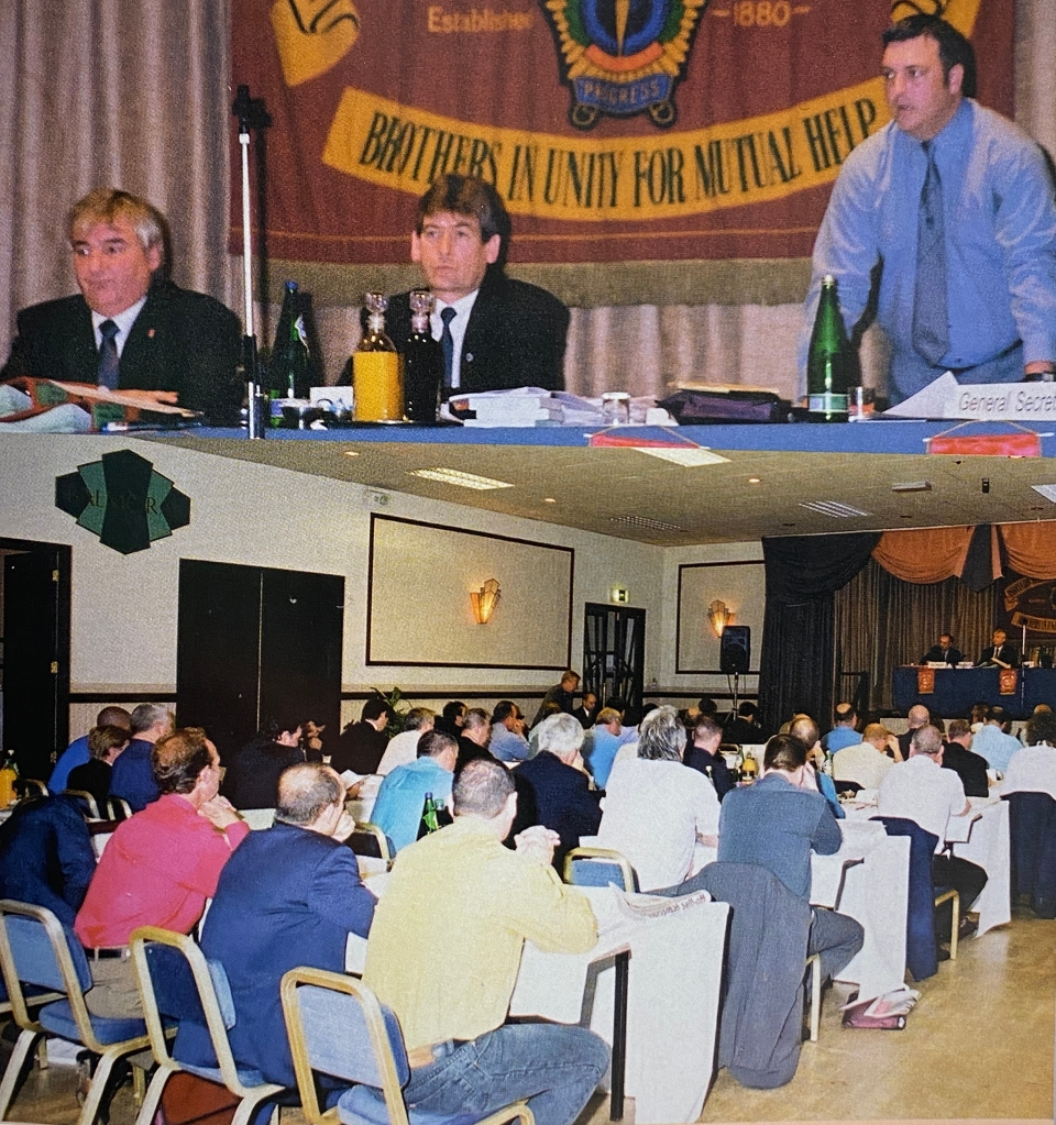 The top half of the picture shows three men on a top table in front of a union banner. The lower half shows a conference room from the back, with delegates sat in rows and three people at the top table.