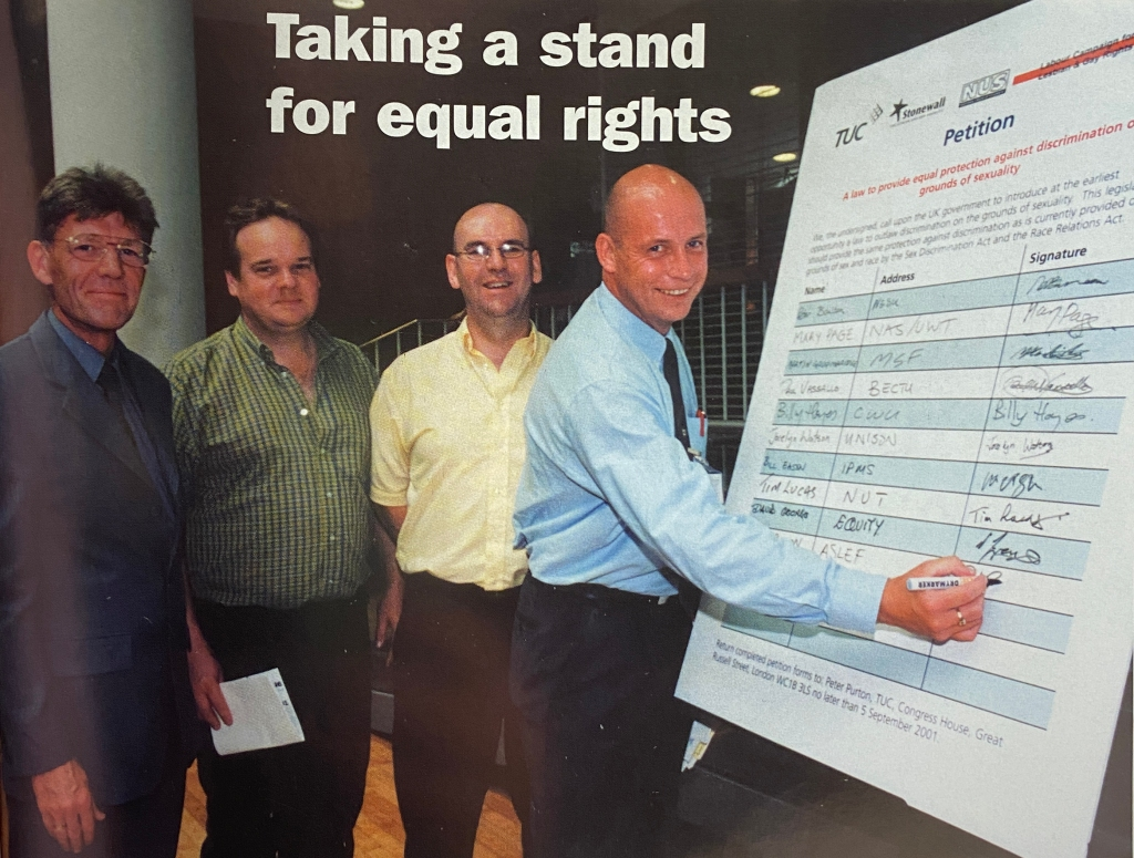 Four men stand together in a hall. On the right of the image, one of the men is signing his name on a large board that says 'petition' at the top.
