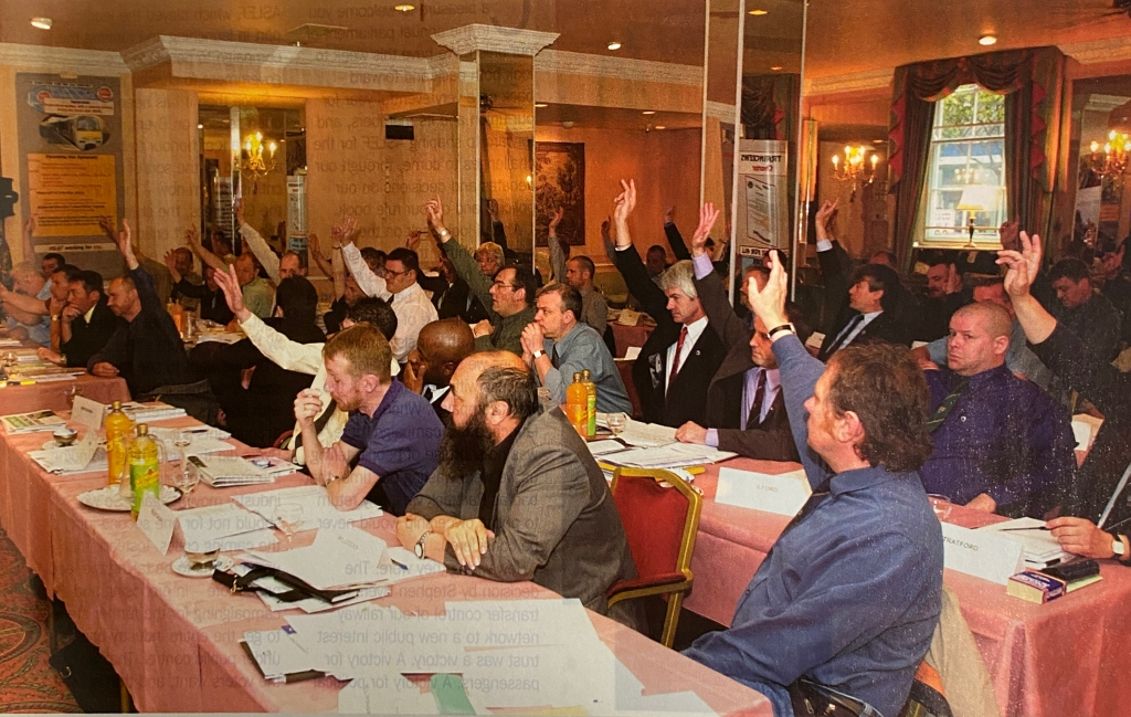 A photograph of bout 50 delegates sitting in rows with paperwork and water glasses on their tables. The majority of the delegates have their hand raised.