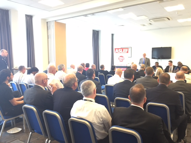 About 50 delegates sit in rows in a conference room. At the front there is a speaker standing up next to a flip chart pad with a large ASLEF logo.