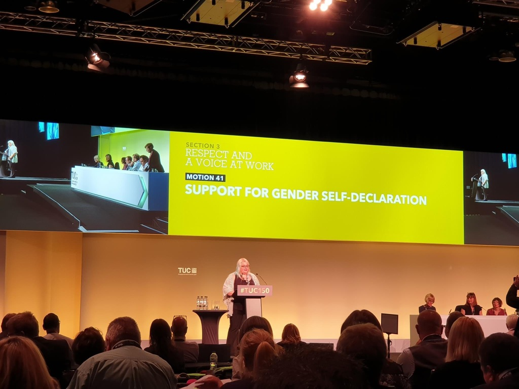 Debbie Reay stands at a lectern branded '#TUC150' and in front of a projected screen with a photograph of a top table and the words 'motion 41: support for gender self-declaration'