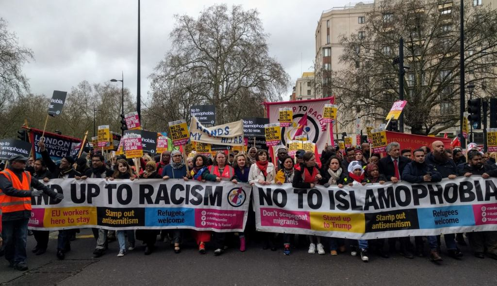 A large group of people including TUC General Secretary Frances O'Grady march with banners and placards. The people at the front are holding large banners saying 'stand up to racism' and 'no to Islamophobia'