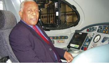 Donald Sewell is photographed sitting on a chair in the driving cab of a train