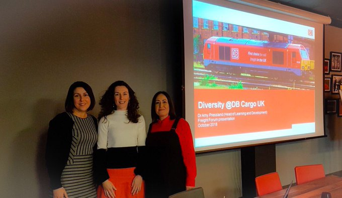Corinne, Amy and Lee stand next to a conference top table next to a project showing a photograph of a freight train and the title 'Diversity @ DB Cargo UK'