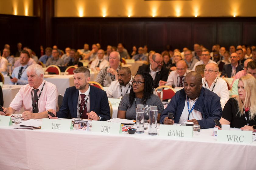 Delegates sit in a full conference hall. On the front row, cards in front of each delegate show that they are representing young members, LGBT+ members, BAME members and women members.