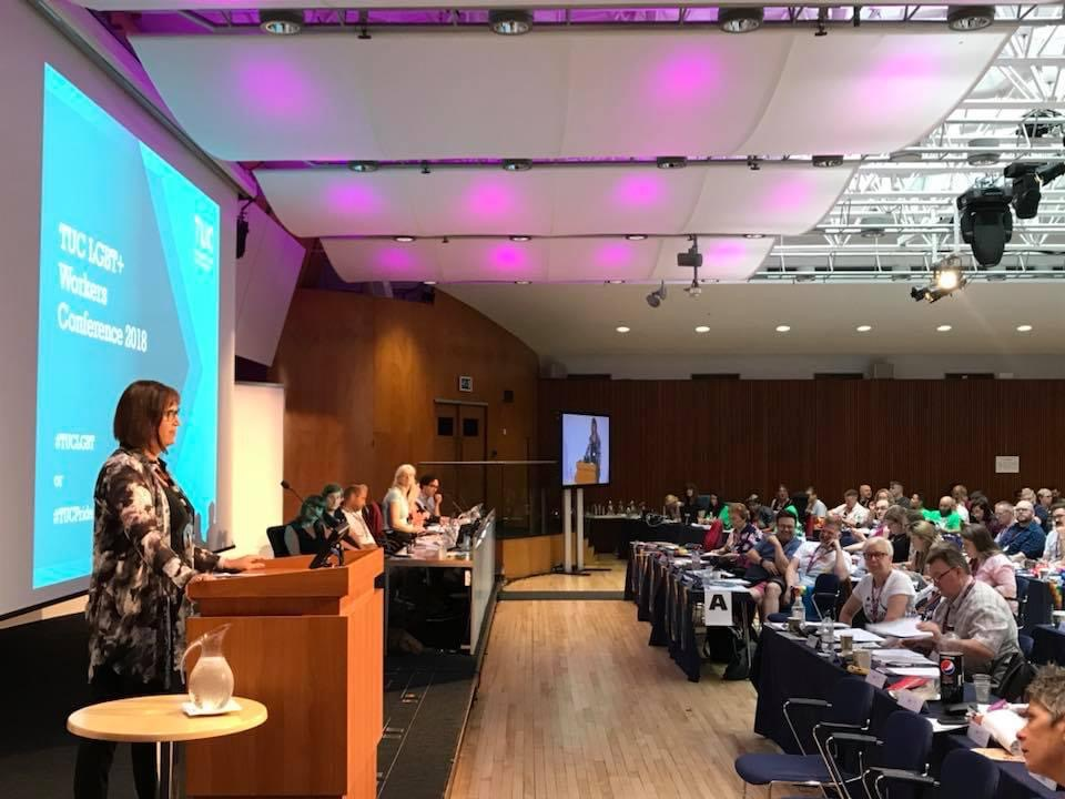 Rachel Harper stands at a lectern in front of a screen saying 'TUC LGBT+ workers conference 2018', and facing a room of delegates