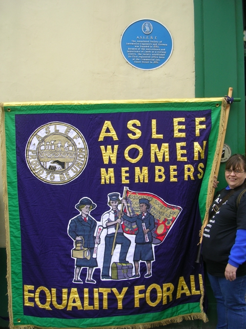 A woman standing under a blue plaque which reads ASLE&F. She is holding one side of a banner which is green and purple and says 'ASLEF Women Members - Equality for All' in gold alongside a picture of three women in work uniforms