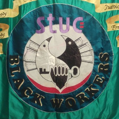 The STUC Black Workers banner. The background is silky turquoise fabric, and in the centre there is a circle in a darker colour with a peace symbol, a hand holding a key and the words 'stuc' and 'black workers'.