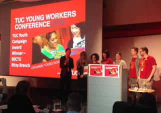 A group of 7 people stand around a podium next to a projector screen showing 'TUC Young Workers conference 2015' and a photograph of three young people talking.